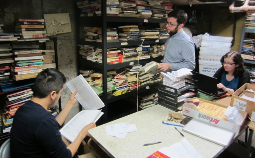 Photo of three people looking through books and papers in a room crowded with bookshelves